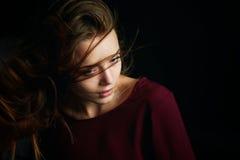 Красивая девушка смотря к стороне, в профиле, летание волос драма Фотография студии в низком ключе на темной предпосылке стоковая фотография rf