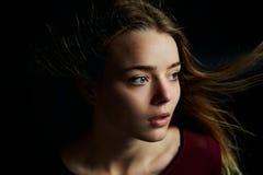 Красивая девушка смотря к стороне, в профиле, летание волос драма Фотография студии в низком ключе на темной предпосылке стоковые изображения