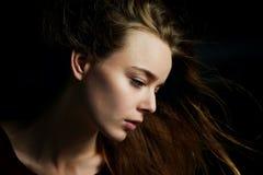 Красивая девушка смотря к стороне, в профиле, летание волос драма Фотография студии в низком ключе на темной предпосылке стоковые изображения rf