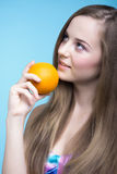 Красивая девушка с апельсином на голубой предпосылке стоковая фотография rf