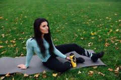 Красивая девушка с бутылкой воды в руку на траве Стоковое Изображение