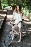 Красивая девушка с велосипедом в парке лета Стоковая Фотография