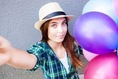 Красивая девушка с воздушными шарами делает фото selfie Стоковые Изображения