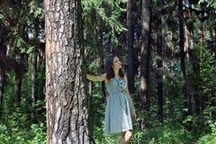Красивая девушка с длинными волосами в платье идя в древесины Стоковая Фотография