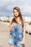 Красивая девушка с длинными шелковистыми волосами в прозодеждах краткости джинсовой ткани Стоковое Фото