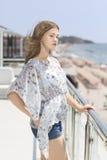 Красивая девушка с длиной, волосы ветра дуя на предпосылке дорогого отеля около моря Очаровательная молодая женщина на море стоковое фото