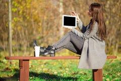 Красивая девушка с компьтер-книжкой в осени паркует outdoors Стоковая Фотография