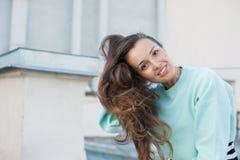 Красивая девушка с коричневыми глазами выправляет волосы сидя на крыше в старом городе стоковая фотография