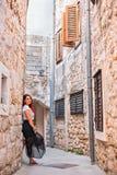 Красивая девушка с красными волосами в платье представляя в одном из города совершает пассаж с много окнами стоковая фотография