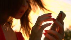 Красивая девушка с красным маникюром используя ее smartphone в парке, теплые цвета захода солнца видео замедленного движения видеоматериал