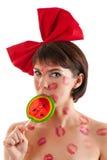 Красивая девушка с красным смычком и леденец на палочке в рте в поцелуях губной помады Стоковые Изображения