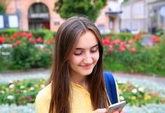 Красивая девушка с мобильным телефоном читает сообщение Стоковое Изображение