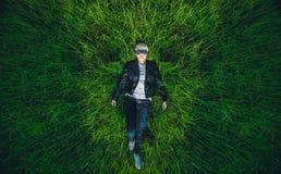 Красивая девушка с светлыми волосами, нося стекла лежит на траве Стоковые Фото