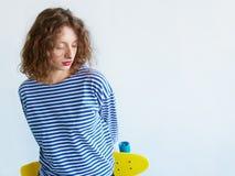 Красивая девушка с скейтбордом в шортах, взглядом от задней части Стоковое фото RF