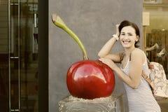Красивая девушка с склонностью рюкзака на огромных искусственных вишнях Стоковое Фото
