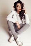 Красивая девушка с темными волосами в вскользь одеждах представляя в студии Стоковые Фотографии RF
