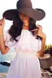 Красивая девушка с темными волосами в элегантной шляпе и белизна одевают Стоковые Фотографии RF