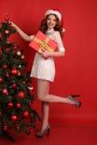 Красивая девушка с темными волосами в элегантном платье с большим подарком на рождество Стоковые Фото