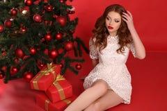 Красивая девушка с темными волосами в элегантном платье с большим подарком на рождество Стоковая Фотография