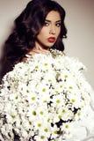 Красивая девушка с темными волосами с большим букетом маргариток Стоковые Изображения RF