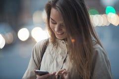 Красивая девушка с телефоном в вечере Стоковая Фотография