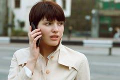 Красивая девушка с телефоном в ее руках Стоковая Фотография RF