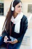 Красивая девушка слушая к музыке в городе Стоковая Фотография