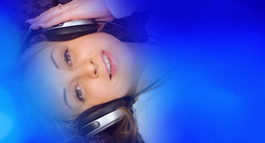 Красивая девушка слушая к музыке на больших наушниках Стоковое фото RF