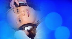 Красивая девушка слушая к музыке на наушниках, предпосылках музыки Стоковые Фотографии RF