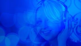 Красивая девушка слушая к музыке с наушниками, голубой предпосылке света bokeh Стоковое Изображение