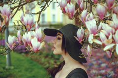 Красивая девушка с черными волосами в черном платье на предпосылке цветка магнолии Стоковые Изображения RF