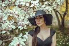 Красивая девушка с черными волосами в черном платье на предпосылке цветка магнолии Стоковое Изображение RF