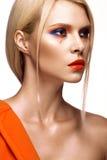 Красивая девушка с яркими покрашенными губами состава и апельсина Сторона красотки стоковое изображение rf