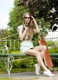 Красивая девушка с longboard сидит на стенде внутри Стоковое фото RF