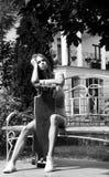 Красивая девушка с longboard сидит на стенде внутри Стоковое Изображение RF