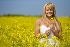 Красивая девушка усмехаясь в поле желтых цветков Стоковое Изображение