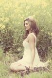 Красивая девушка усмехаясь в поле желтых цветков Стоковое фото RF