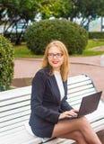 Красивая девушка усмехаясь с компьтер-книжкой Стоковая Фотография RF