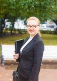 Красивая девушка усмехаясь с компьтер-книжкой Стоковая Фотография