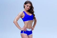 Красивая девушка фитнеса в голубом нижнем белье спорта представляет на белой предпосылке Стоковое фото RF