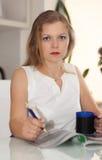 Красивая девушка читая кассету и выпивая кофе Стоковые Фотографии RF