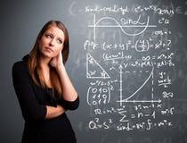 Красивая девушка школы думая о сложных математически знаках Стоковые Фотографии RF