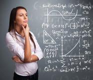 Красивая девушка школы думая о сложных математически знаках Стоковая Фотография