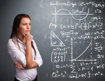 Красивая девушка школы думая о сложных математически знаках Стоковое фото RF