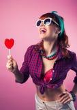 Красивая девушка штыря-вверх представляя с красным в форме сердц agai леденца на палочке Стоковое Фото