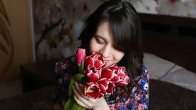 Красивая девушка для того чтобы обнюхать цветки, смотрящ камеру, усмехаться, flirting акции видеоматериалы