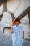 Красивая девушка redhead нося в striped рубашке представляя против предпосылки бетонной стены Стоковые Изображения RF