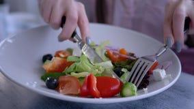 Красивая еда диеты, женские руки с ножом и вилка отрезали свежий огурец в греческом крупном плане салата акции видеоматериалы