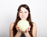 Красивая еда молодой женщины овощи держащ капусту, она вытаращится на голове капусты здоровая еда - здоровая Стоковые Изображения RF