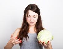 Красивая еда молодой женщины овощи держащ капусту, она вытаращится на голове капусты здоровая еда - здоровая Стоковые Изображения